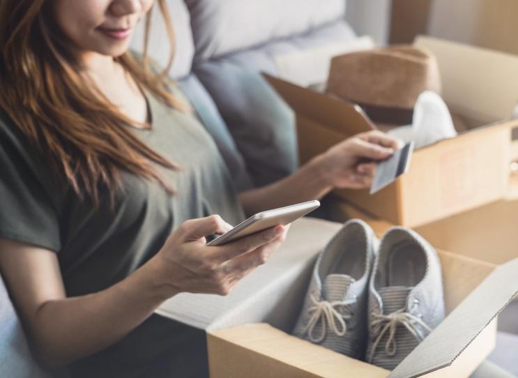 Femme avec smartphone et paire de chaussure