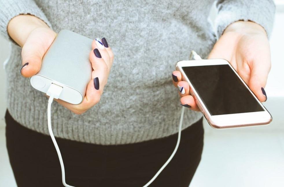 Femme_qui_tient_un_iphone_et_une_batterie_externe